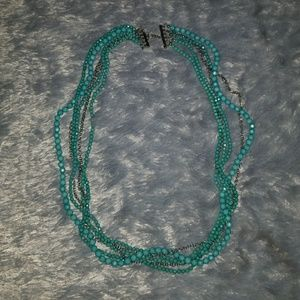 Turquoise colored necklace entertwined with silver